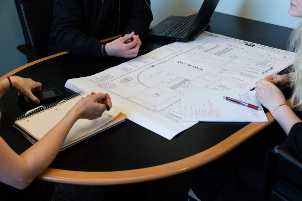 top 5 remodeling mistakes to avoid: people around table looking over remodel plans