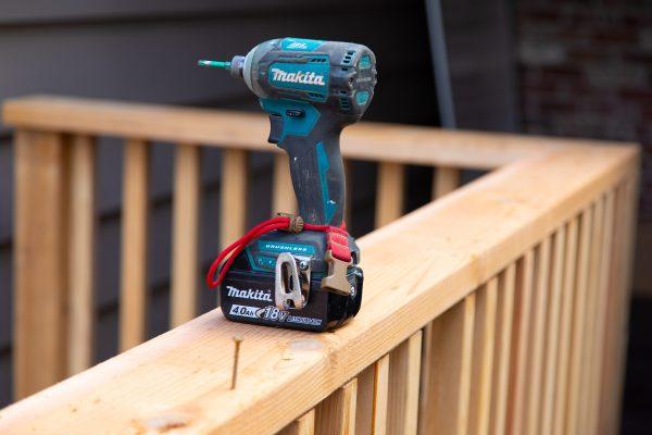 drill sitting on wood deck railing