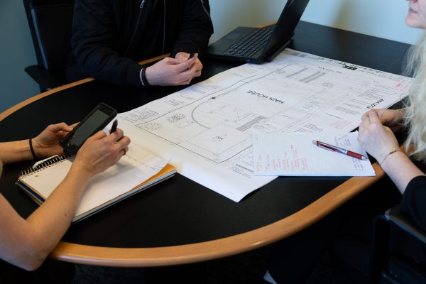 home renovation timeline: people working around table with remodel plans