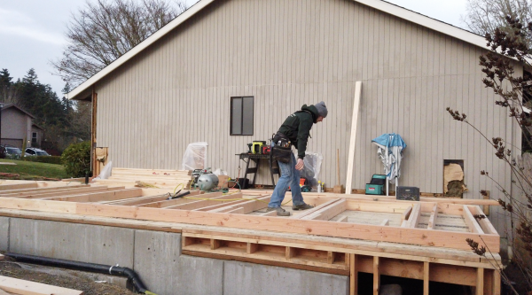 home renovation timelime: product delays. Worker installing wood framing on new addition