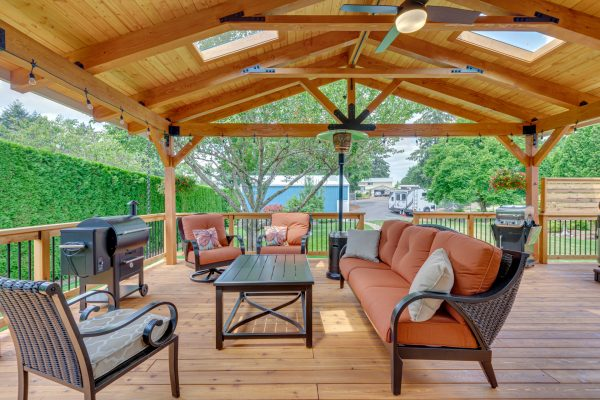 new outdoor deck with sofas, barbecue, and wood covered ceiling