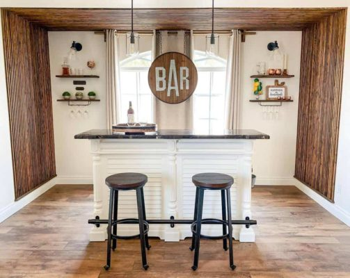 modern home bar ideas: small bar with sign and two chairs